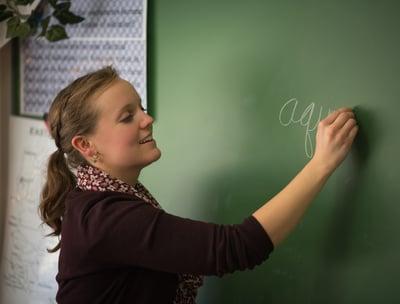 3rd grade teacher using chalkboard to instruct