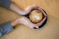 Woman holding cup of coffee on table in cafeteria