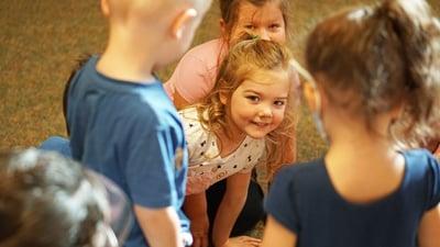 girl-peeking-through-group-smiling
