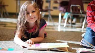 girl-reading-on-floor-smiling